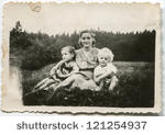 stock-photo-vintage-photo-of-mother-with-children-sitting-on-grass-fifties-121254937