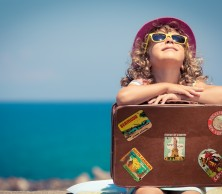 child on holiday in sun with suitcase