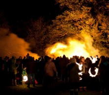 Crowds of people gathered around a blazing bonfire celebrating Bonfire Night or Guy Fawkes on the 5th November