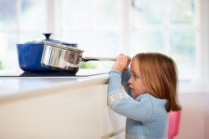girl pulling down saucepan